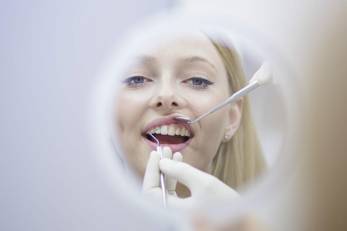 patienten in der zahnarztpraxis stuttgart schaut in den spiegel währende der untersuchung